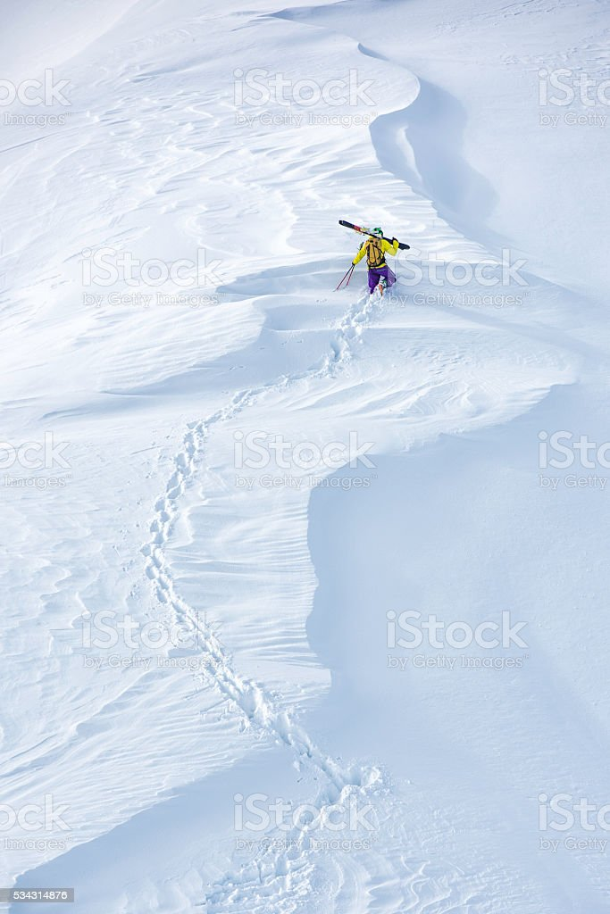 Skier climbing up a hill stock photo
