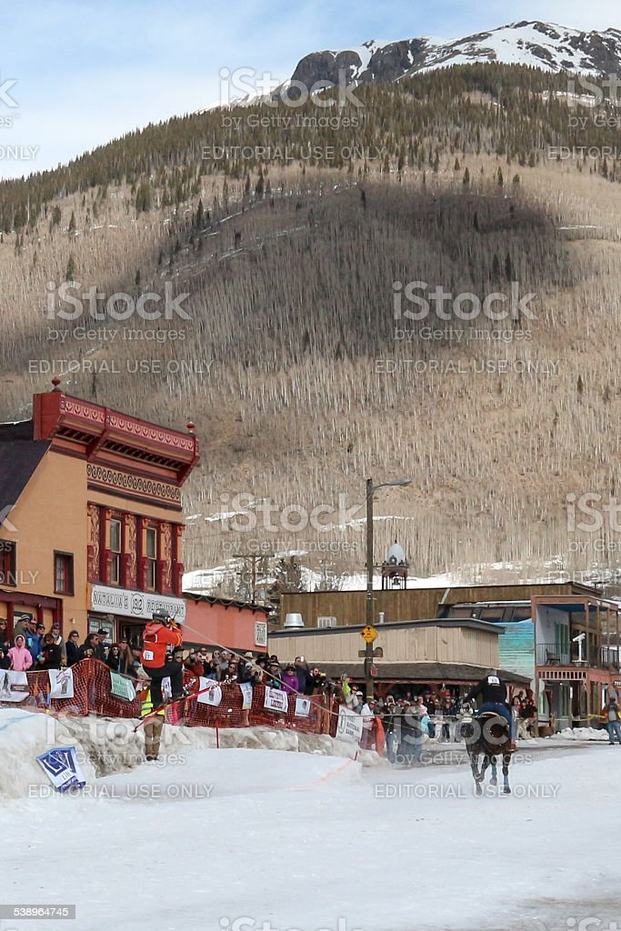 Skier coming off a jump at a skijoring competition stock photo