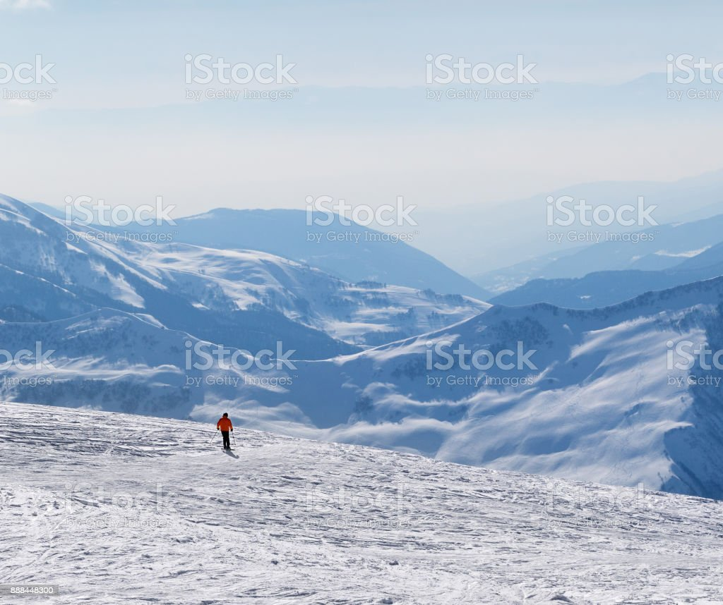 Skier downhill on snowy off-piste slope and mountains in haze stock photo