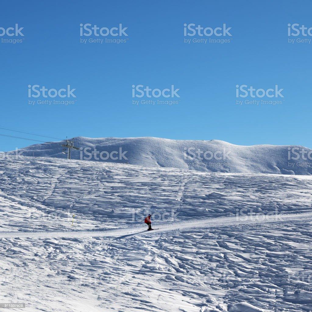 Skier downhill on snowy ski slope at nice sun morning stock photo