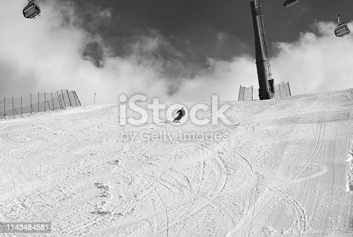 Skier downhill on snowy ski slope at sun winter day. Caucasus Mountains, Shahdagh, Azerbaijan. Black and white toned image.