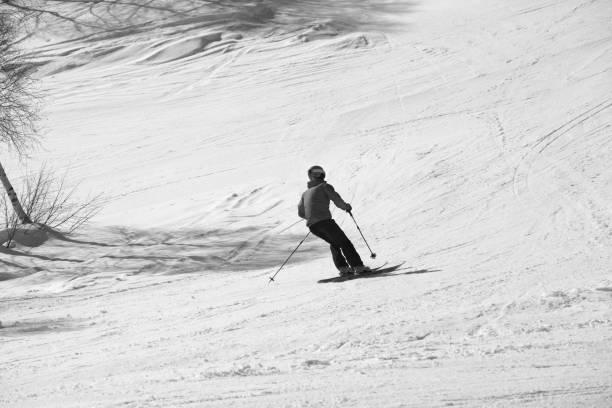 Skier downhill on snowy ski slope at sunny day - foto stock