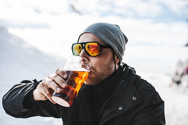 Skier drinking a beer at after ski Skier drinking a beer at after ski apres ski stock pictures, royalty-free photos & images