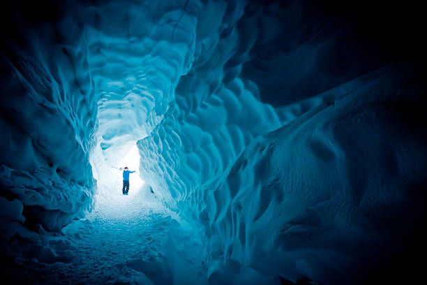 Skier exploring ice cave. Male carrying skis on shoulders, walking out from glacier cave. explorer stock pictures, royalty-free photos & images