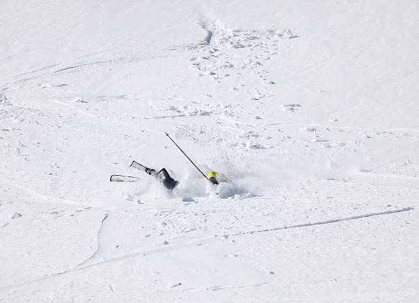 Skier falling down on mountain slope stock photo