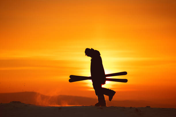 Skier goes with ski in hands against sunset