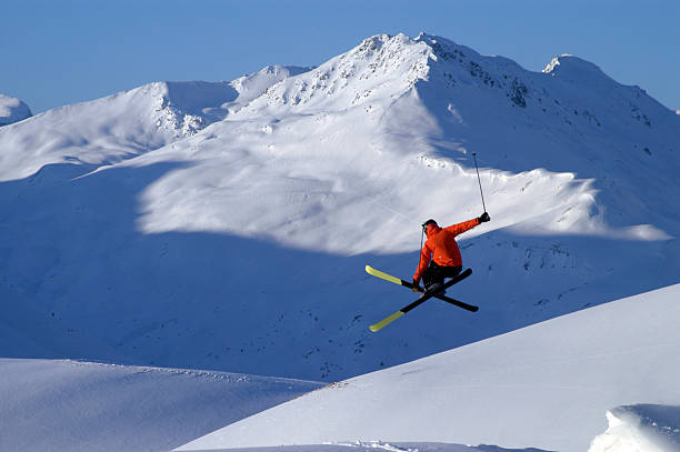 A skier in a red jacket performing a jump stock photo