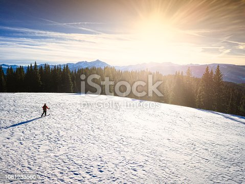 Skier in Backcountry Skiing Scenic Mountain Landscape - Man out enjoying the outdoors solo on a ski tour at sunset with panoramic mountain views. Vail, Colorado USA.