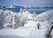 Skier above beautiful alpine lake - Lake Tahoe - in winter with a fresh snowfall covering the trees and distant mountains of the Sierra
