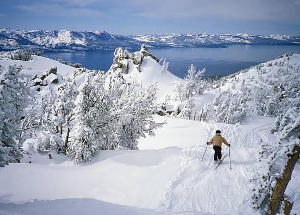skifahrer in fresh snow über alpine lake tahoe - lake tahoe winter stock-fotos und bilder