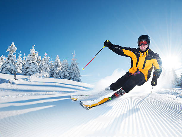 Skier in mountains, prepared piste and sunny day stock photo