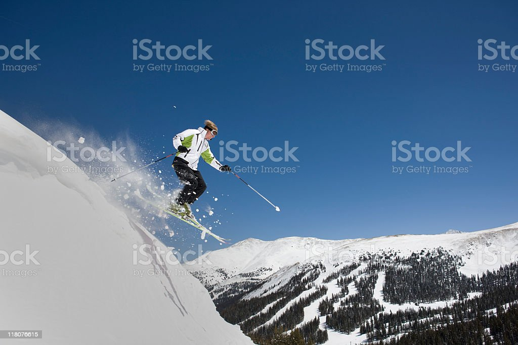 Skier Jumping Against Blue Sky and Mountains royalty-free stock photo