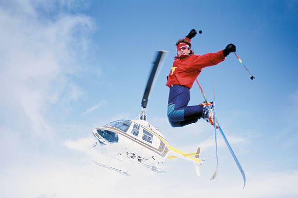 Skier jumping from helicopter stock photo