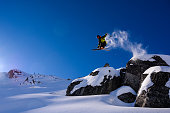 Male athlete jumping off of rocks into fresh powder. Ski vacations in Canada.