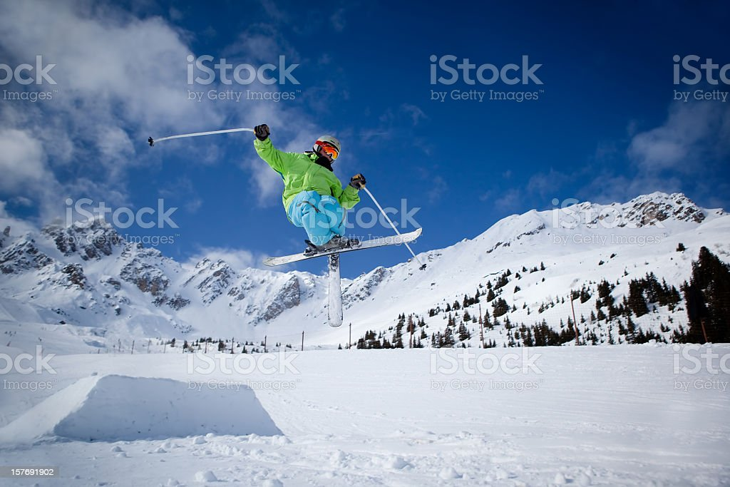 A skier jumping over a small mound stock photo