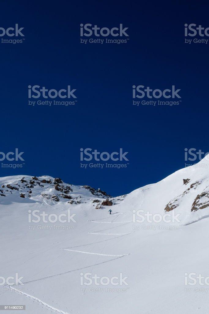 Skier leading way up steep slope to alpine mountain pass stock photo