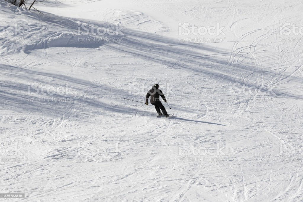 Skier on ski slope at sun winter day stock photo