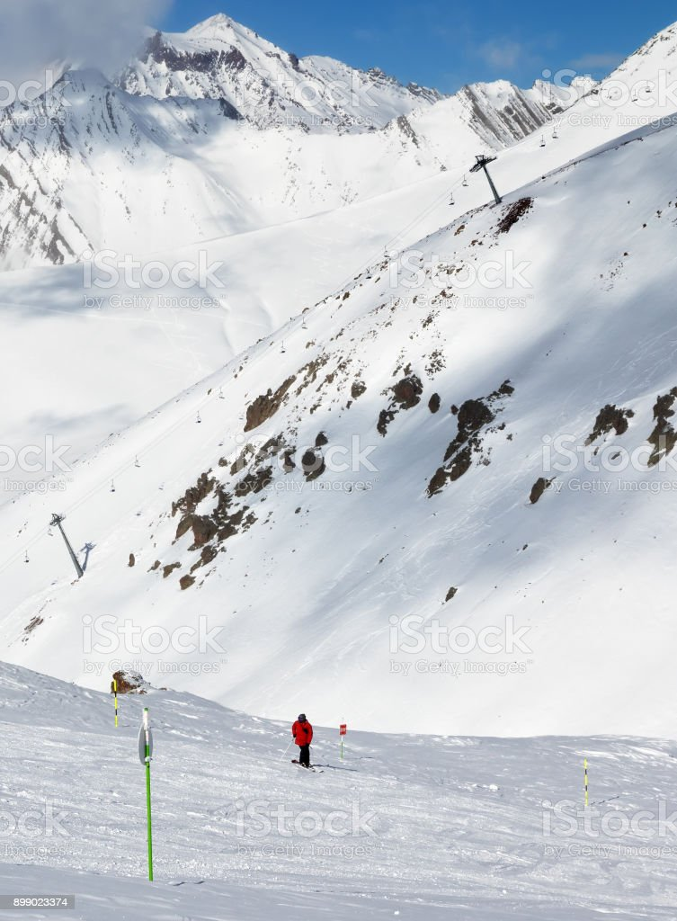 Skier on snowy ski trace and mountains in clouds stock photo