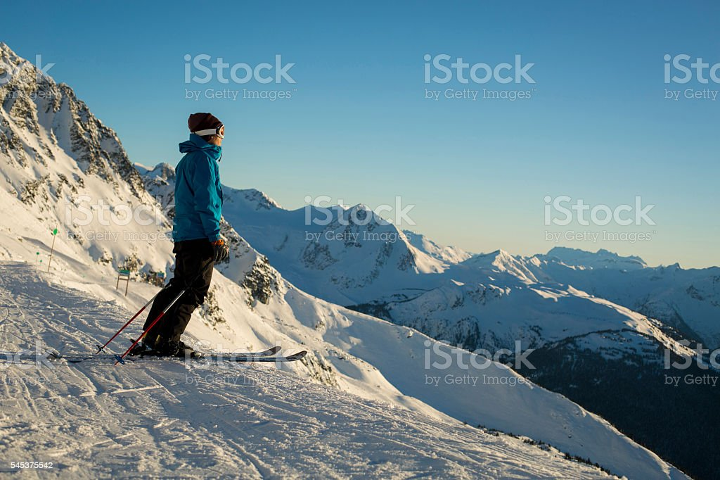 Skier on top of mountain looking into sunset. stock photo