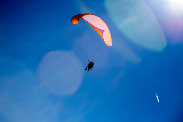 Skier Paragliding with skis using a selfie stick while flying through bright lens flair with blue sky and plane trails in the sky stock photo