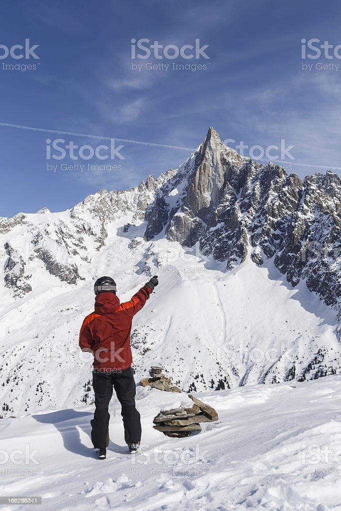 Skier pointing towards mountain peak royalty-free stock photo