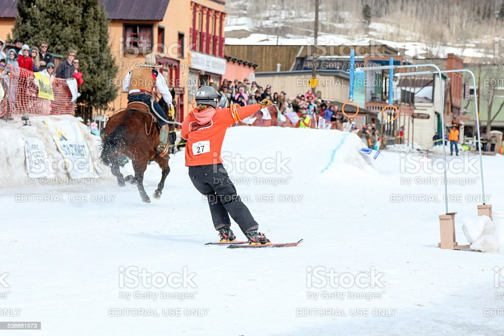 Skier reaching for rings on a skijoring course stock photo