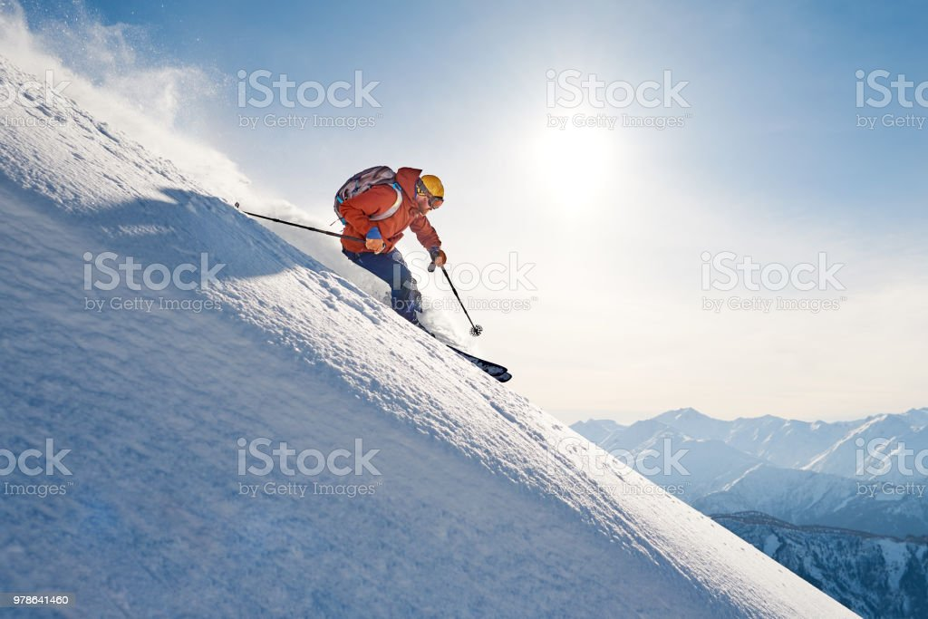 skier rides freeride on powder snow down slope against the backdrop of the mountains stock photo