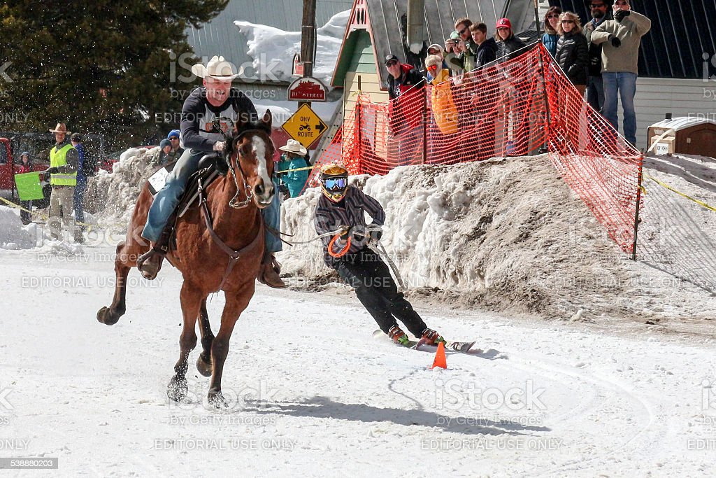 Skier rounding a slalom cone in a skijoring competition stock photo