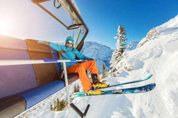 Skier sitting at ski chair lift in Alpine mountains stock photo