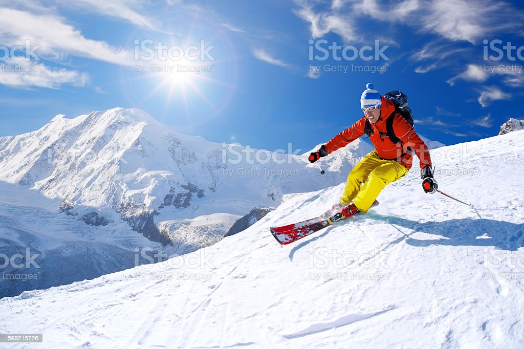 Skier skiing downhill against Matterhorn peak in Switzerland stock photo