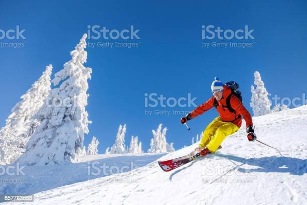 Skier skiing downhill in high mountains against blue sky picture id857763588?b=1&k=6&m=857763588&s=612x612&h=93vwd1yirnn yxmdzbxmqvlkmsf5yh71n thh4w3fym=