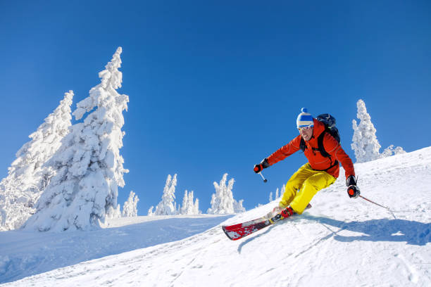 Skier skiing downhill in high mountains against blue sky Skier skiing downhill in high mountains against blue sky ski stock pictures, royalty-free photos & images