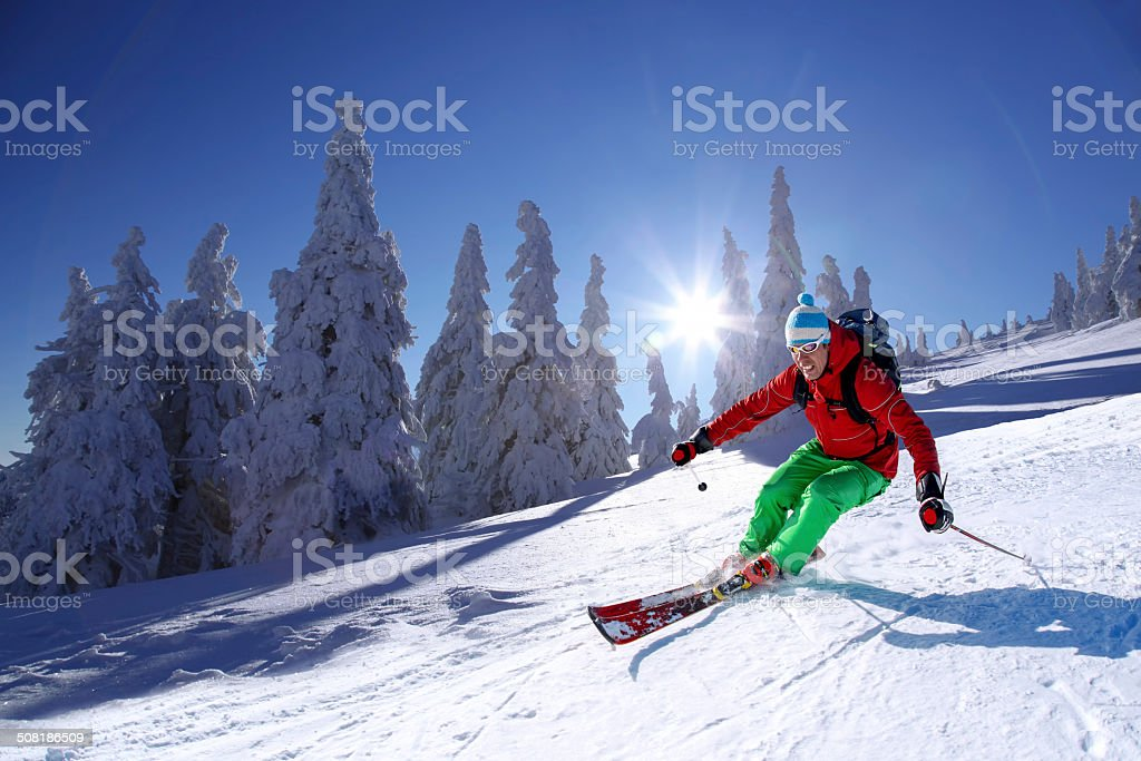 Skier skiing downhill in high mountains against sunset stock photo