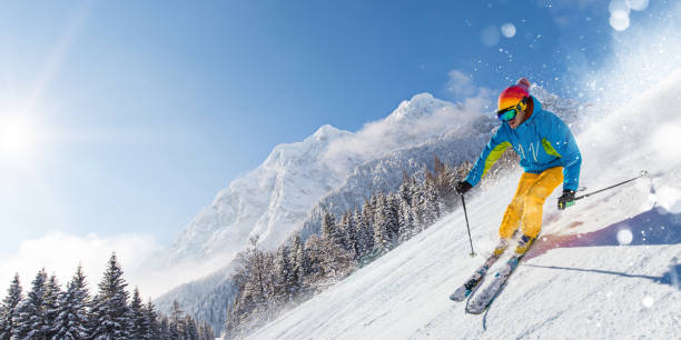 Skier skiing downhill in high mountains Skier skiing downhill during sunny day in high mountains ski stock pictures, royalty-free photos & images