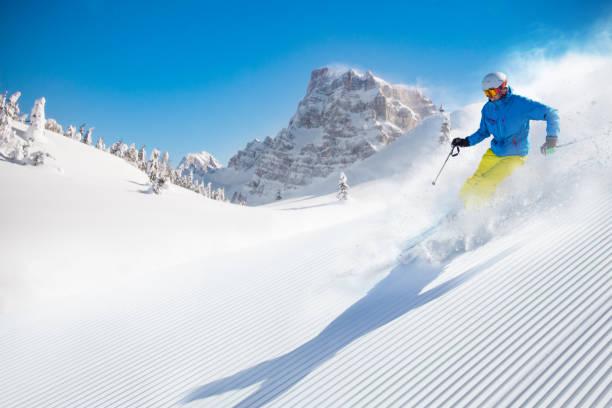 skiër afdaling skiën in de hoge bergen - skipiste stockfoto's en -beelden