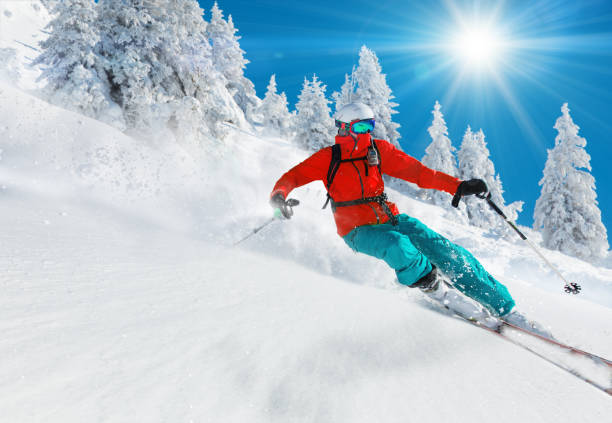 Skier skiing downhill in high mountains Skier skiing downhill in high mountains during sunny day. ski stock pictures, royalty-free photos & images