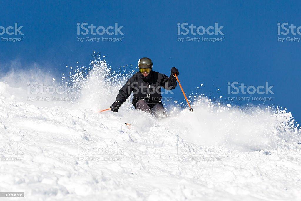 Skier skiing off piste in powder snow stock photo