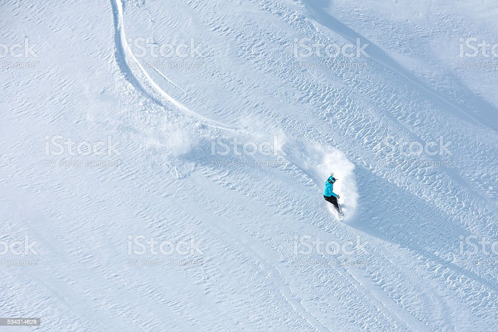 Top view of a free skier descending down a snowcapped hill, copy...