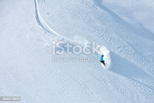 Top view of a free skier descending down a snowcapped hill, copy space.