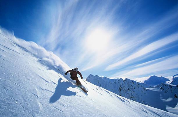 Skier Skiing On Mountain Slope stock photo