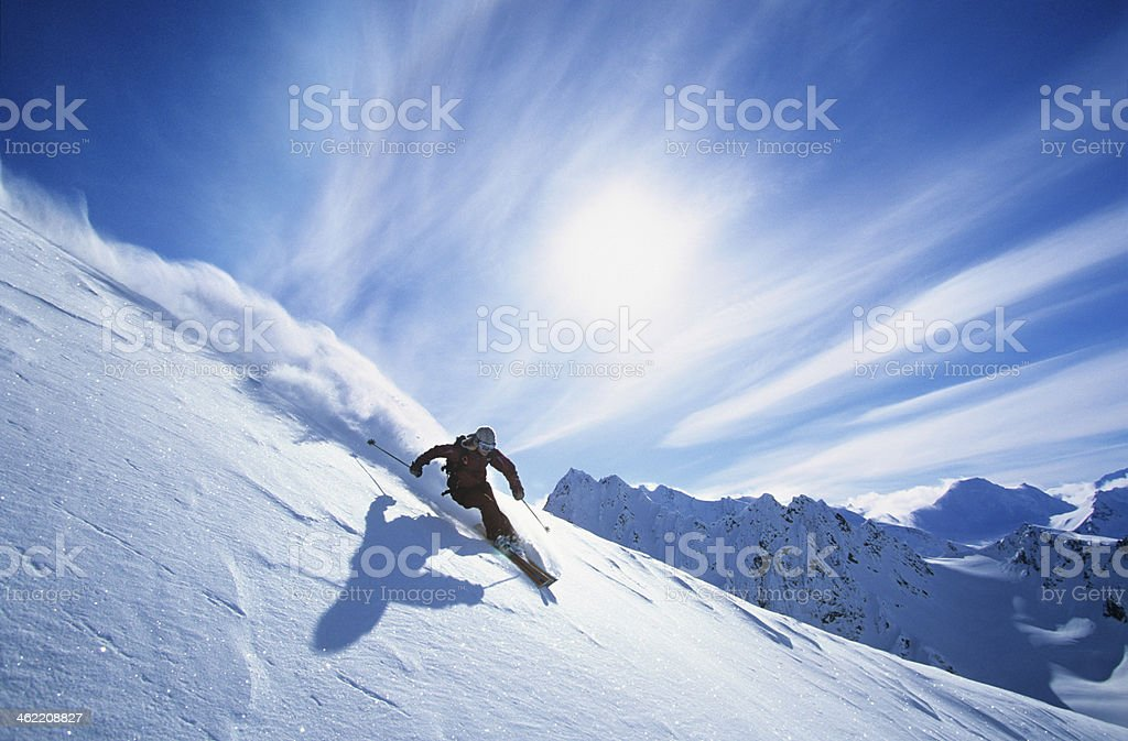 Skier Skiing On Mountain Slope stock photo