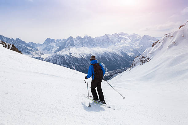 Skier skiing on snowy slope in Alps mountains near Chamonix Skier skiing on red slope in Alps mountains near Chamonix, France ski holiday stock pictures, royalty-free photos & images