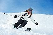 Woman free skiing in fresh powder in Laax, Switzerland.