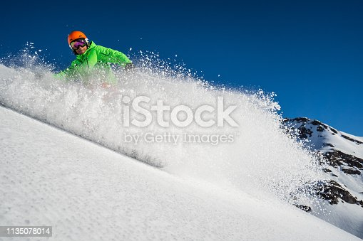skier on fresh empty slope dusting powdering camera with snow