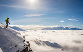 A skier in the Swiss ski resort of Verbier standing on top of a cliff above a sea of clouds, looking towards Mont Blanc and Chamonix.