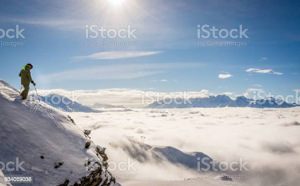 Photo of Skier standing on a rock above the clouds