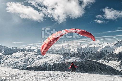 Davos, Switzerland - February 19, 2018: A skier prepares his parachute for speedriding. Speedriding is a new extreme sport and combines skiing with paragliding.. The photo was taken in Switzerland on the Jakobshorn. The Jakobshorn is a very well-known ski area above Davos. Davos itself is known as a winter holiday destination and above all the annual World Economic Forum (WEF) takes place here.