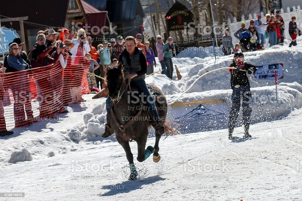 Skier sticks the landing in a equestrian skijoring competition stock photo