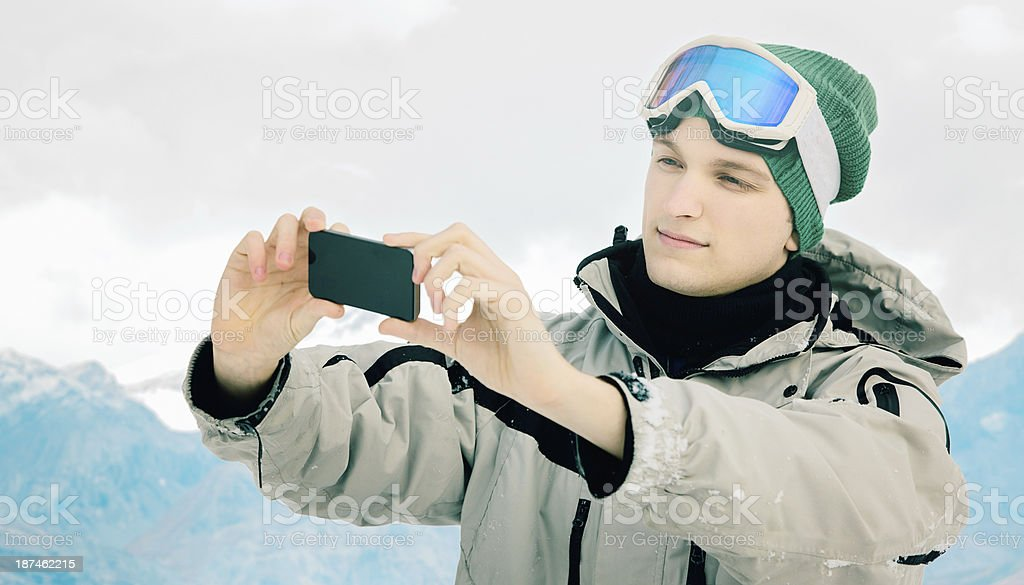 Skier taking a picture with his phone royalty-free stock photo