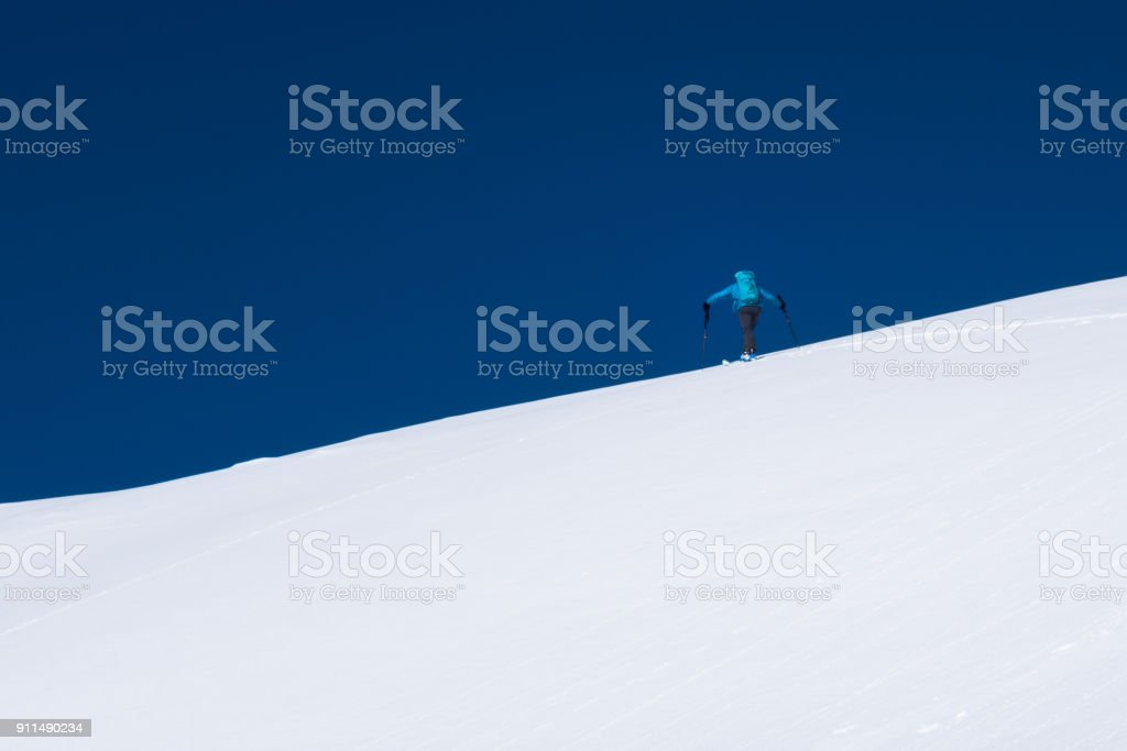 Skier touring up a snow covered alpine ridge in winter stock photo